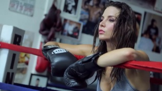 Kacey Barnfield holding the ropes of a boxing ring and looking into the distance