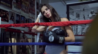 Kacey Barnfield running her hands through her hair in a boxing ring