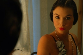 Kacey Barnfield smiling in front of a mirror dressed in vintage clothing