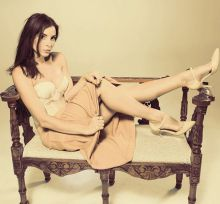Actress Kacey Barnfield lying back on a couch with her legs up