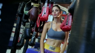 Kacey Barnfield standing in a boxing gym wearing a gray sports bra