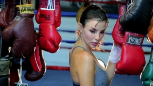 Kacey Barnfield looking over her shoulder next to boxing gloves