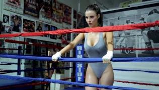 Kacey Barnfield in a gray bodysuit with her hands on the ropes of a boxing ring