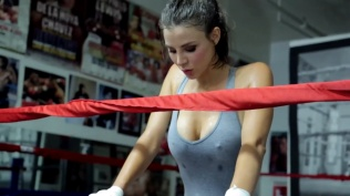 Kacey Barnfield holding the ropes of a boxing ring and looking down