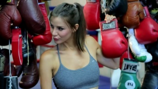 Kacey Barnfield holding a boxing glove and giving a sexy smile