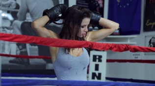 Kacey Barnfield raising her arms in a boxing ring