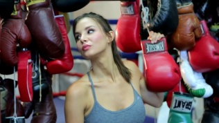 Kacey Clarke tilting her head back and holding a boxing glove