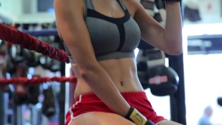 Close-up of Kacey Barnfield's hot body wearing a gray sports bra and red shorts