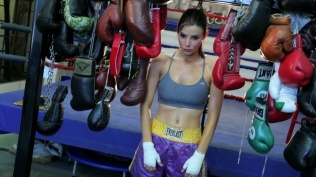 Kacey Barnfield standing in a boxing gym wearing a sports bra and boxing shorts