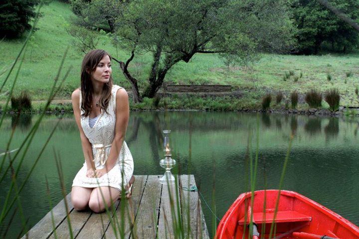 Kacey Barnfield kneeling next to a lake