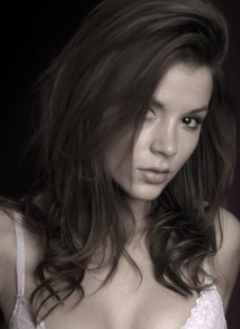 Close up shot of Kacey Barnfield looking cute in front of a dark back ground