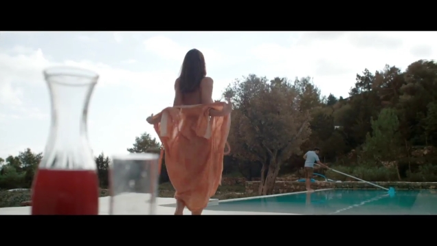 Kacey Barnfield about to reveal her naked body by a pool