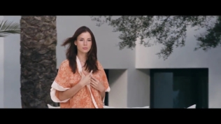 Kacey Barnfield walking to a pool in a robe