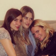 Kacey Barnfield with two friends on a sofa