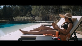 Kacey Clarke reading a book while sunbathing