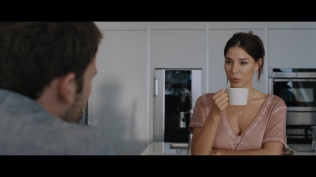 Kacey Clarke about to drink from a cup opposite Ben Lamb in a kitchen