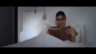 Kacey Clarke wearing reading glasses and holding a book in bed