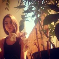 Kacey Clarke behind a plant