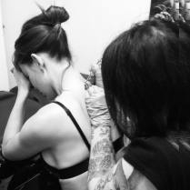 Kacey Clarke getting a tattoo on her back