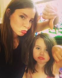 Kacey Clarke and a cute little girl doing a thumbs down gesture