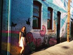 Kacey Clarke standing by some graffiti on a wall