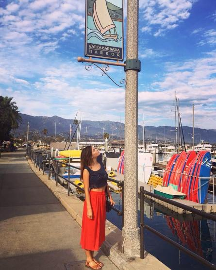 Kacey Clarke under a sign that says Santa Barbara